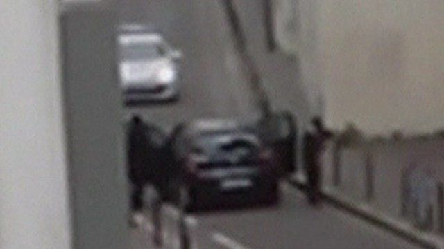 The Kouachi brothers aiming their guns at a police car