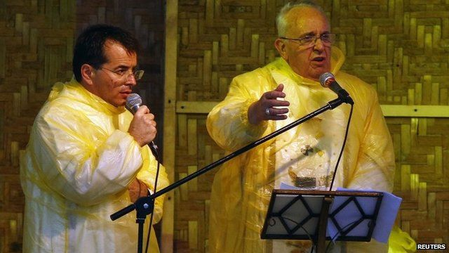 Pope Francis and translator in plastic ponchos