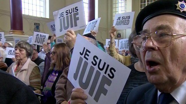 Crowd holding signs saying Je Suis Juif