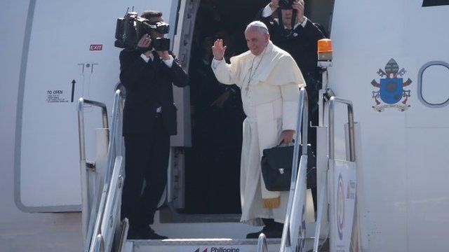 Pope Francis waves from the steps of his aircraft as he leaves Villamor Airbase for Rome