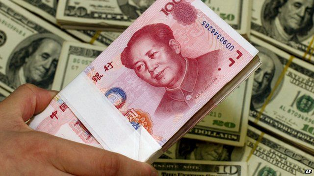 Close up of pack of bills of Chinese yuan on top of piles of US dollars