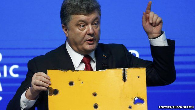 Ukraine President Petro Poroshenko, speaking at World Economic Forum in Davos, holds a fragment of a bus body which he says shows a Russian missile attack on a civilian bus