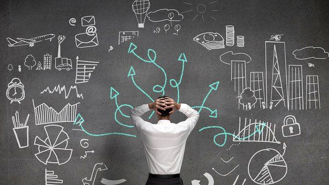 Man standing in front of board with diagrams drawn on