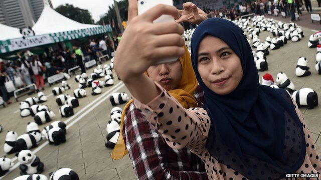 Two Muslim women in headscarves pose while one takes a self portrait