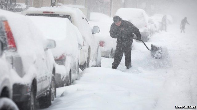 A man digs out his car along a snow-covered street