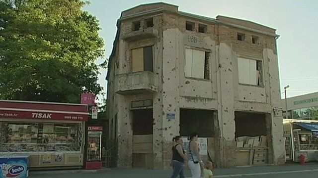 Building riddled with bullet holes as family walk past