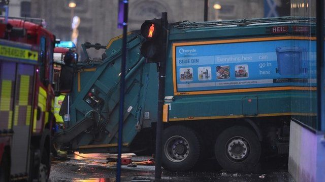 Emergency service trucks are parked near a bin lorry at the scene of the crash