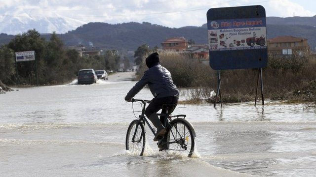 A boy rides his bicycle through a flooded street in the village of Mifol