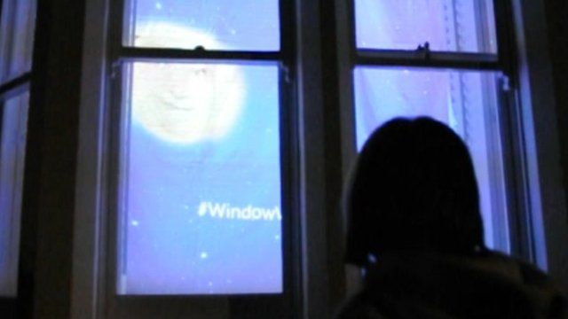 Amelia Spooner interacts with the moon face on the Window Wanderland art trail in Bristol