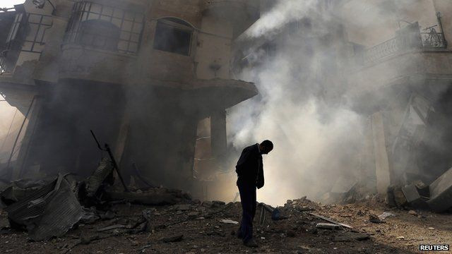 A man (with head bowed) walks in front of a burning building after a Syrian Air force airstrike in Ain Tarma neighbourhood of Damascus in this January 27th 2013