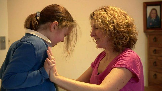 Mum Debbie Fisher helps her daughter with exercises