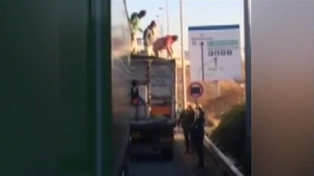 Migrants getting down off lorry