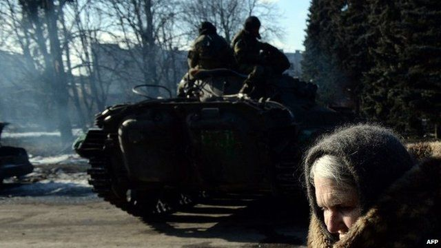 An elderly woman walks past a rebel armoured personnel carrier in the eastern Ukrainian town of Debaltseve, 20 February