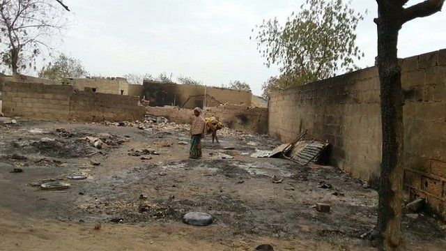 File photo of girl standing amid the burned ruins of Baga, Nigeria, following an attack by Boko Haram