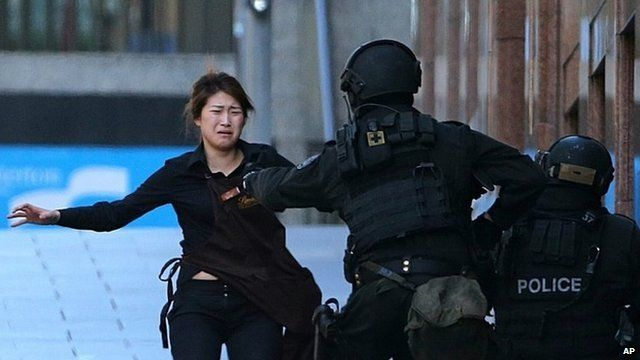 Bae Jie-un, a staff member of a Sydney cafe and one of the hostages, runs to armed tactical response police officers for safety after she escaped from a cafe under siege in Sydney