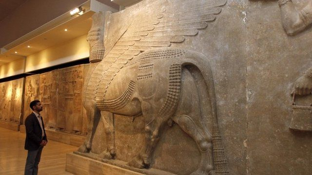 A man looks at ancient Assyrian human-headed winged bull statues at the Iraqi National Museum in Baghdad