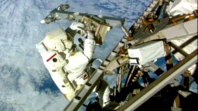 Astronaut tinkers with space station equipment
