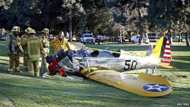 Emergency service personnel stand next to Harrison Ford's vintage plane after it crashed on a golf course in Venice, California - 5 March 2015
