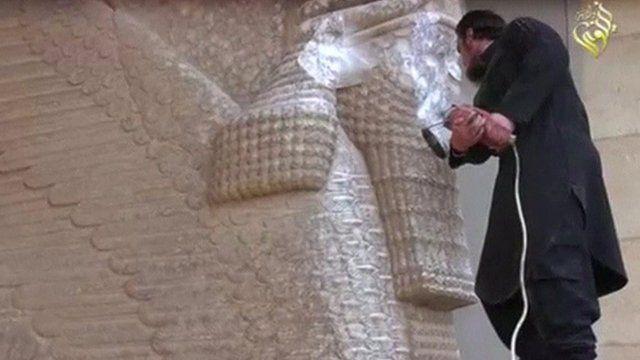 An IS militant destroys a statue