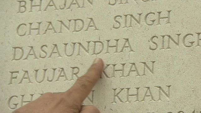 Close up of hand pointing to name, Dasaundha Singh (an Indian soldier who died saving a British officer) on Neuve Chapelle war memorial