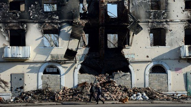 People walk past a building damaged in fighting in Vuhlehirsk, just south of Debaltseve