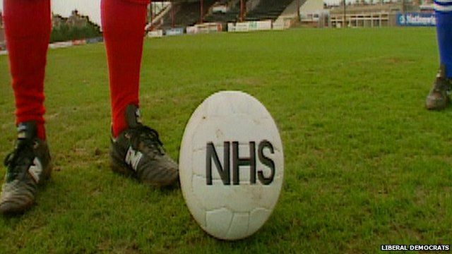 A football with NHS emblazoned on it is kicked between a player in red and a player in blue.