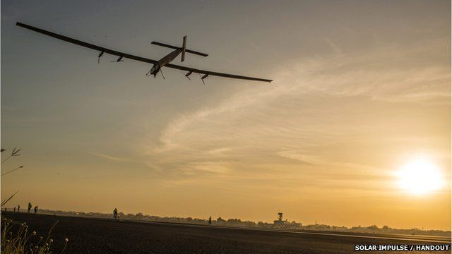 File photo of Solar Impulse flying in the sky as the sun sets to the right of it