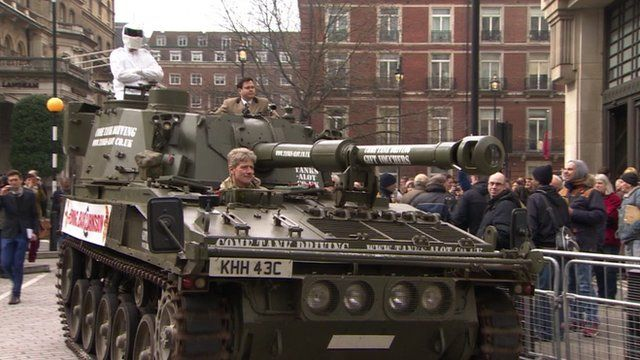 A tank with a man dressed as Stig on it