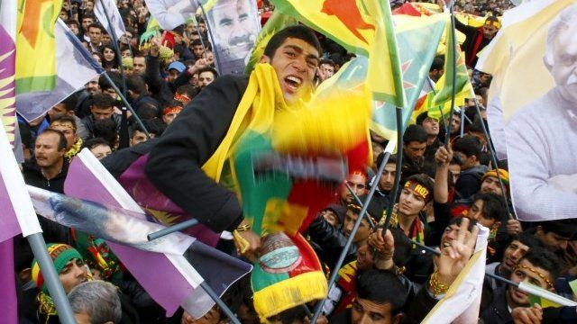 People gesture while others wave Kurdish flags