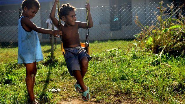 Children play on a swing in Vanuatu