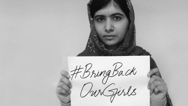 Malala Yousafzai holds up a sign saying Bring Back Our Girls