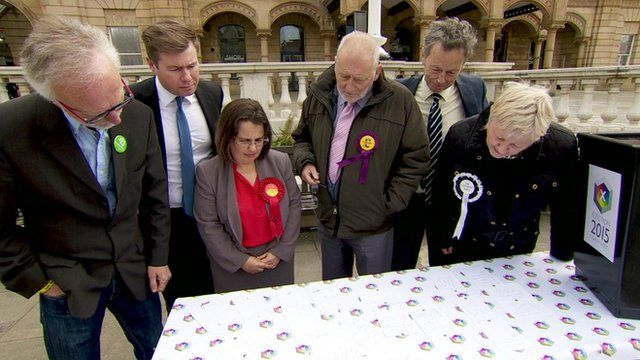 Election candidates look at papers on table