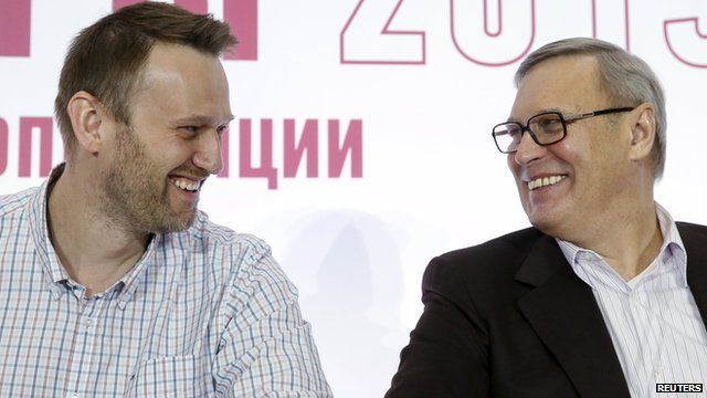 Russian opposition leaders Alexei Navalny (L) and Mikhail Kasyanov smile at each other during a joint news conference