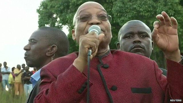 South African president Jacob Zuma addressing foreigners waiting in a camp after fleeing xenophobic violence