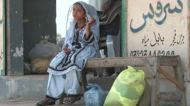 Young girl in Gwadar, Pakistan sitting outside a shop