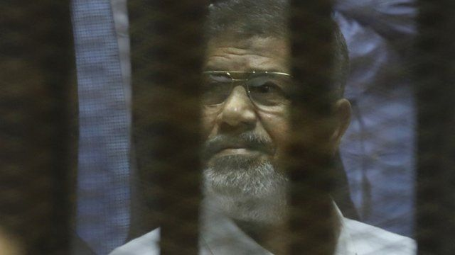 "Egypt""s ousted Islamist President Mohammed Morsi sits in a soundproof glass cage inside a makeshift courtroom at Egypt's national police academy in Cairo, Egypt, Tuesday, April 21, 2015"