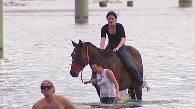 A woman riding a horse through flood water