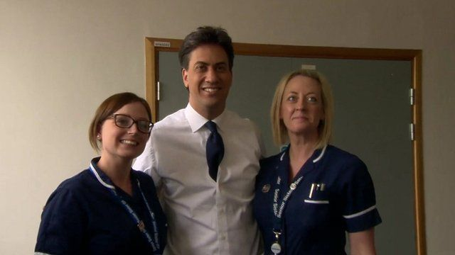 Ed Miliband flanked by a two nurses