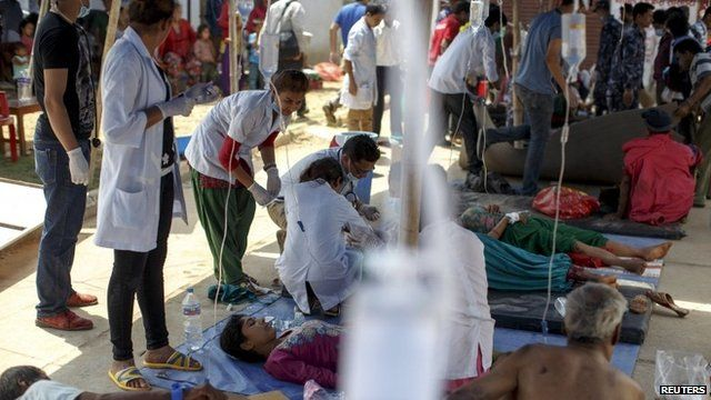 Earthquake victims receive medical treatment outside the overcrowded Dhading hospital