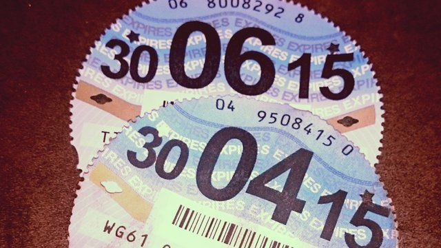 Close up of two tax discs (with expiry dates in June and April 2015)