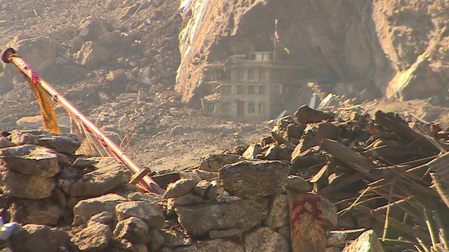 Rubble in Langtang with remains of only building still standing in background
