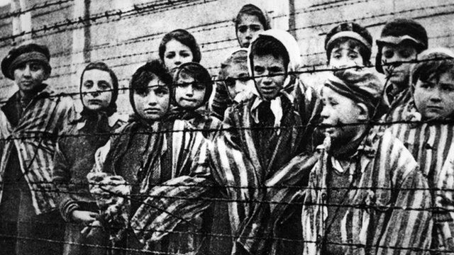Children behind a barbed wire fence at the Nazi concentration camp at Auschwitz in southern Poland. Undated.