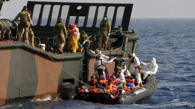 HMS Bulwark staff help refugees adrift in the Mediterranean onto a Royal Navy Landing Craft in the Mediterranean taken on 7 May 2015