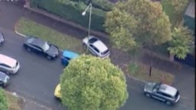 A car mounts the pavement during a police chase