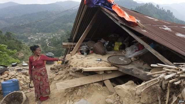 A Nepalese woman stands next to a temporary shelter after an earthquake stuck Nepal