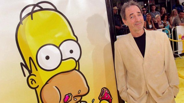 Harry Shearer next to a poster of The Simpsons