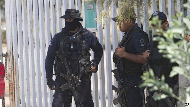 Mexican state police stand guard near the entrance of Rancho del Sol, near Vista Hermosa