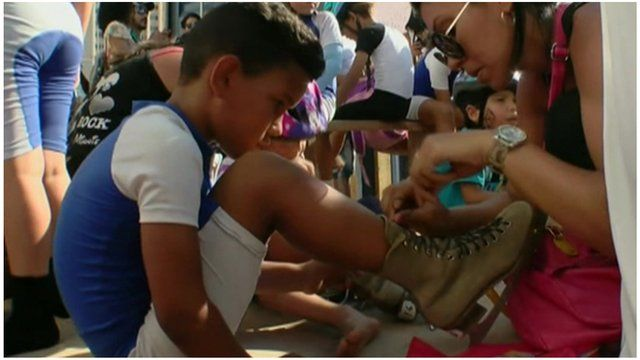 A child gets their laces tied