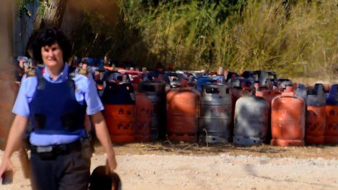 Una agente de los Mossos d'Esquadra, junto a bombonas de butano almacenadas