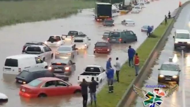 People standing on a central reservation look at submerged vehicles on a flooded road during stormy weather in Durban, South Africa, 10 October 2017